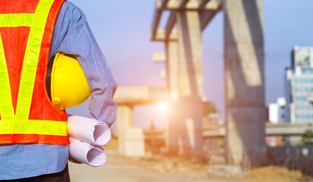 engineer holding yellow safety helmet in building construction site